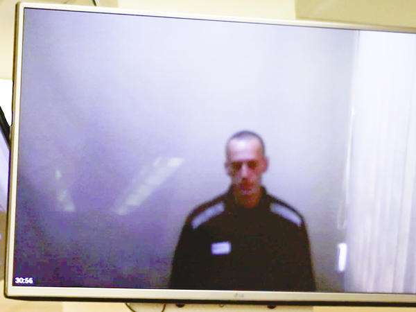 In this photo taken from a video provided by the Babushkinsky District Court in Moscow on Thursday, Russian opposition leader Alexei Navalny is seen during a hearing on charges of defamation.