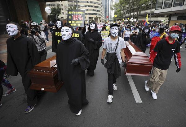 Protesters wearing Guy Fawkes masks carry empty coffins during a national strike to protest a government proposal that would raise taxes, in Bogotá, Colombia, on Wednesday.