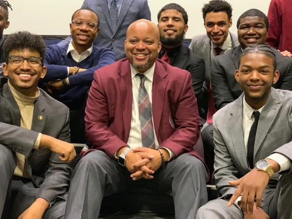 Members of the Morehouse College speech and debate team at the 2019 Pi Kappa Delta National Championship at Hofstra University. Coach Kenneth Newby is seen at the center, and student debater Daniel Edwards is at front left.