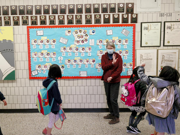 Students wave goodbye during dismissal at Yung Wing School P.S. 124 on March 25, 2021 in New York City.