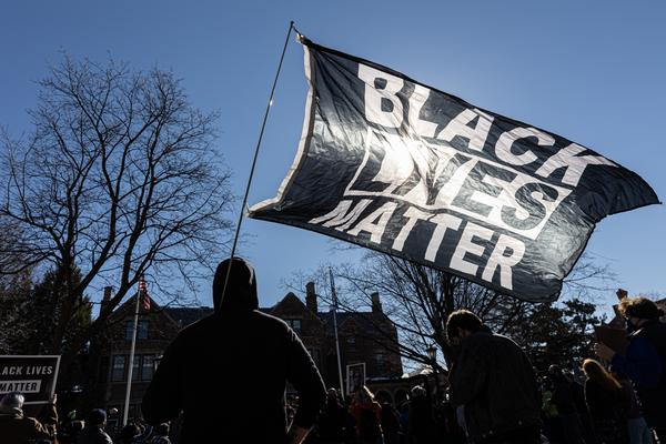A man holds a Black Lives Matter flag during a March protest in St. Paul, Minn. Support for Black Lives Matter surged after protests following George Floyd's death. Activists charge that disparaging posts targeting BLM are part of an overall effort to undermine the movement and its message.