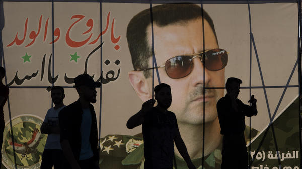 Men walk in front of a campaign poster for Syrian President Bashar Assad whose government announced Thursday that he had won reelection.
