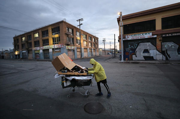 A homeless man pushes his belongings along a Los Angeles street.