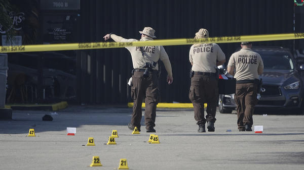 Miami-Dade Police work the scene of a shooting outside a banquet hall near Hialeah, Fla., Sunday. Two people died and an estimated 20 to 25 people were injured.