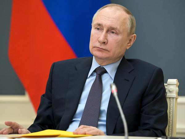 "Russian President Vladimir Putin attends a meeting Wednesday via video link. The sanctions against Moscow signal that ""we are going to be clear to Russia that there will be consequences when warranted,"" the White House press secretary says."