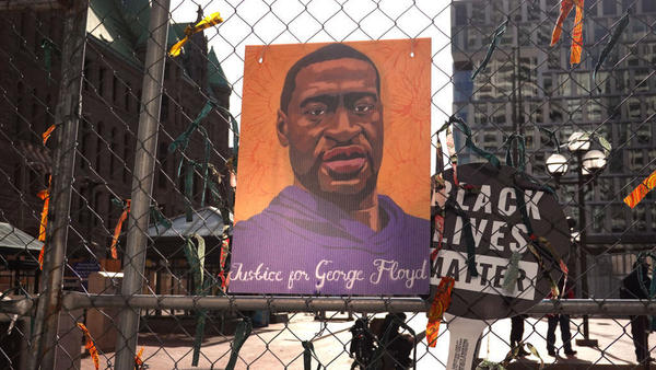 A picture of George Floyd hangs on a fence barrier that surrounds the Hennepin County Government Center in Minneapolis during the trial of former police officer Derek Chauvin in March. The Justice Department is now bringing criminal charges against Chauvin over allegedly violating Floyd's rights and using excessive force in restraining him.