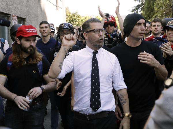 """In this 2017 photo, Gavin McInnes (center), founder of the far-right extremist group known as the Proud Boys, is surrounded by supporters after speaking at a rally in Berkeley, Calif. McInnes told NPR that the group is made up of """"funny dudes, not Nazis."""" At least 25 members of the far-right group are facing charges related to the Jan. 6 attack on the Capitol."""