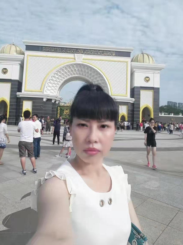 """A selfie taken by Feng Daoyou. Her older brother Feng Daokun believes she traveled to Hong Kong before flying to the U.S., from where she first contacted him in 2016. Unlike the rest of her family, she did not marry, and seemed to relish venturing far from home. """"She could do anything she put her mind to. She was tough. She never gave up. That was just her personality,"""" her brother says."""