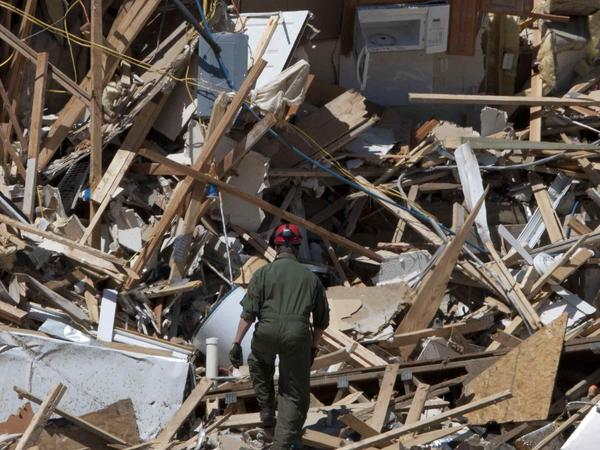 In this file photo taken May 4, 2011, Tuscaloosa Fire Lt. Brian Phillips climbs a pile of rubble in search of survivors or bodies at an apartment building in Tuscaloosa, Ala. On April 27, 2011, a series of tornadoes killed hundreds of people, injured thousands and reduced countless buildings to rubble across a swath of the U.S.