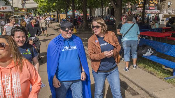 "Minnesota's state demographer, Susan Brower (center), walks with Dean Goldberg, donning a blue cape and black mask as ""Census Man,"" through the 2019 Minnesota State Fair in St. Paul, Minn., to encourage residents to participate in the national head count."