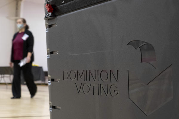 A worker passes a Dominion Voting Systems ballot scanner during Georgia's runoff Senate elections in January in Gwinnett County outside Atlanta. Former President Donald Trump and his allies spread falsehoods about the company's role in the 2020 election, leading to a slew of defamation lawsuits.