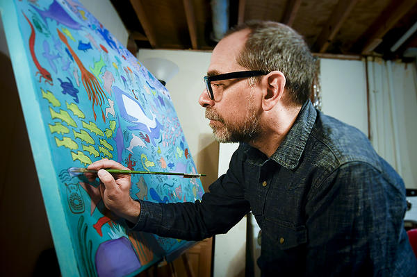 Working in his basement studio, Howard Rains adds a bit of  color to a squid-like creature in his basement studio.