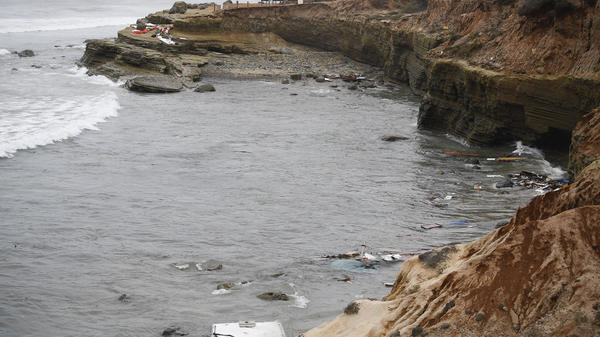 Wreckage from a capsized boat washes ashore at Cabrillo National Monument near where a boat capsized off the San Diego coast Sunday. Authorities say four people were killed and two dozen others injured.
