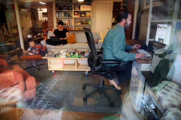 Seth, right, and Nicole Kroll work on their computers while their son Louis, 5, entertains himself at their home in the Jamaica Plain neighborhood of Boston, MA on April 14, 2020. (Craig F. Walker/The Boston Globe via Getty Images)