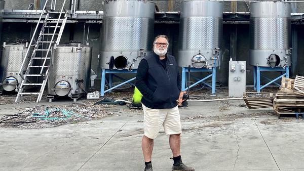 Owner and founder Jeff Smith in front of what remains of Hourglass' winery and processing facility in California's Napa Valley. He's rebuilding, but wildfires have him rethinking everything about his land and business.