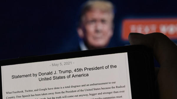 A statement from former President Donald Trump is seen in front of his Facebook page background. Facebook was justified in its decision to suspend Trump after the Jan. 6 insurrection, the company's Oversight Board said Wednesday.