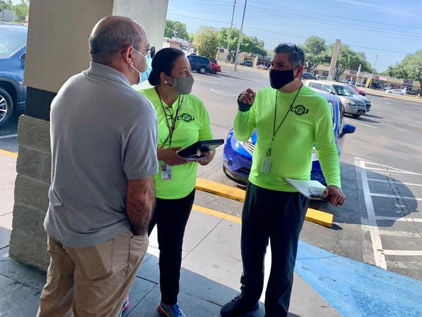Oswaldo Simon, left, said he appreciated the help state canvassers provided signing him up for a COVID-19 vaccine appointment in his neighborhood.