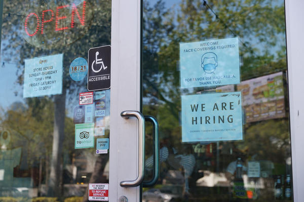 """A """"We are hiring"""" sign is paired with a pandemic-themed sign in the window of a store in Miami. Restaurants and other in-person businesses are looking to hire more workers at a time when some are wary of returning to work or are busy with caregiving."""