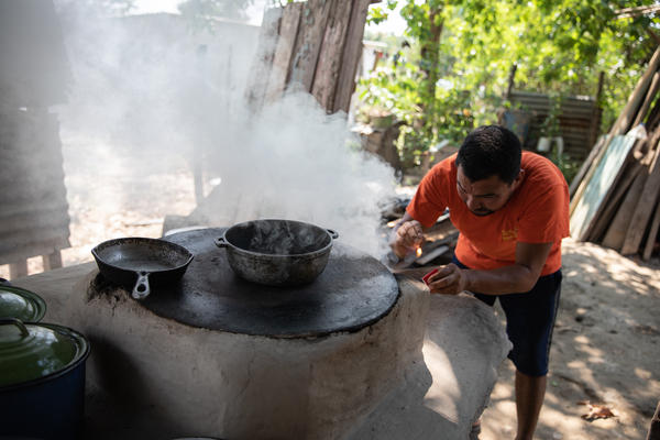 Adan Ramos lights the wood-fired stove that his wife, Blanca Marisa Balegas, uses to make tortillas, the family's only source of income after the hurricanes destroyed their home and neighborhood.