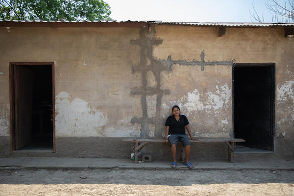 Glenda Ramos sits in front of her home in La Independencia, La Lima. The force of the 2020 hurricanes collapsed the street-facing wall of the house.