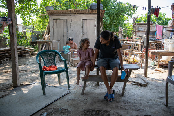 Glenda Ramos speaks with her niece, Allison, while her brother, Adan, builds furniture for the family. The Ramos family lost everything after hurricanes Eta and Iota swept through northern Honduras in late 2020.
