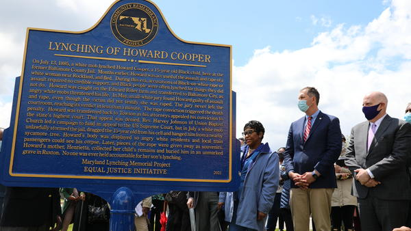 Maryland Gov. Larry Hogan, far right, Baltimore County Executive John Olszewski and Maryland House Speaker Adrienne Jones stand next to a new historic marker on Saturday in Towson, Md., that memorializes Howard Cooper, a 15-year-old who was dragged from a jailhouse and hanged by a mob in 1885.