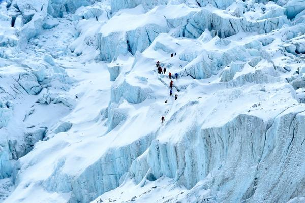 """China will set up a """"line of separation"""" at Mount Everest's summit, as Nepal struggles to control a COVID-19 outbreak. In this photograph, on May 2, 2021 mountaineers trek along the Khumbu glacier near Everest base camp in the Mount Everest region of Solukhumbu district, some 140 km northeast of Nepal's capital Kathmandu."""