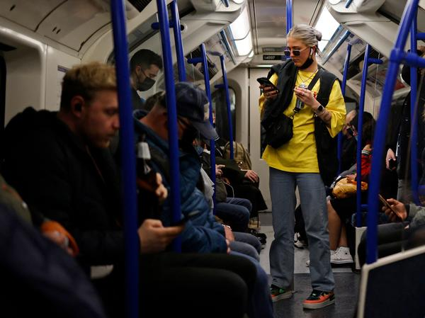 Passengers, some wearing protective face coverings and some not, travel during rush hour on the London Underground last month.