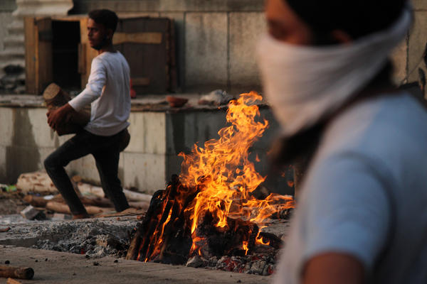 In New Delhi on Monday, family members cremate the body of a person who died after contracting COVID-19.