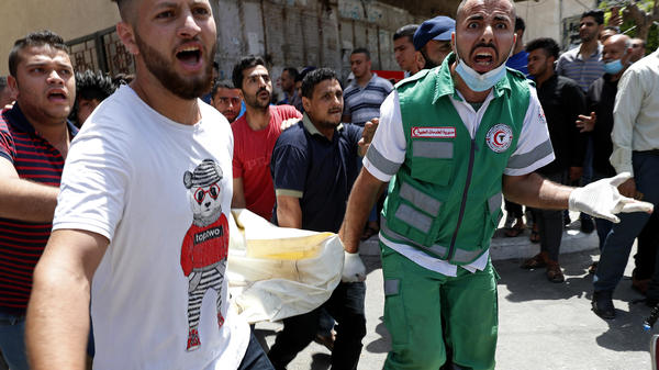 Medics and youths chant slogans while carrying the covered body of a man who Palestinian officials say was killed in Israeli airstrikes on his apartment building Tuesday in Gaza City.