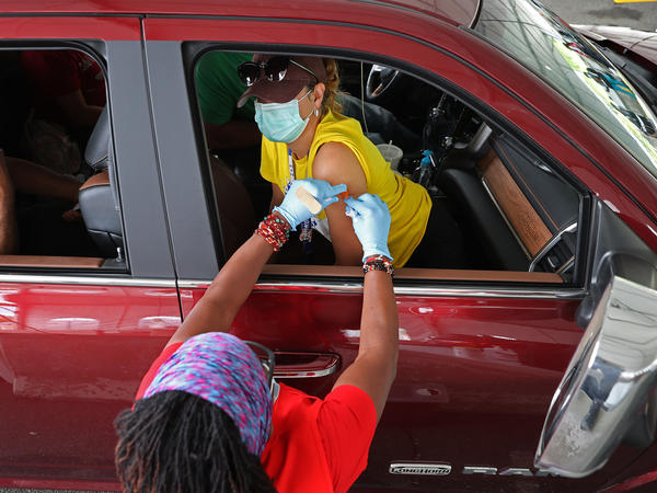People who need help getting to a vaccination site will be able to get free or discounted rides through Uber and Lyft, the White House says. Here, a woman receives her first dose of the Pfizer vaccine at a mass vaccination site in Aberdeen, Md., after getting a ride to the site from her landlord.