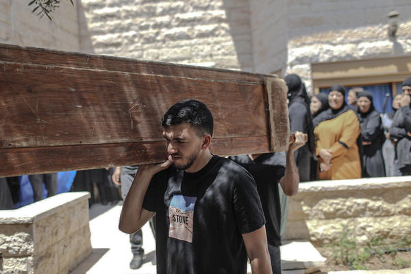 Mourners carry the coffin of Khalil Awad, 52, at the funeral for him and his 16-year-old daughter, Nadin Awad. The two Palestinian citizens of Israel were killed early Wednesday when a rocket fired from the Gaza Strip hit their home in Dahmash, a village near the city of Lod, Israel.