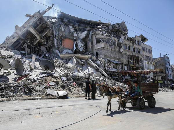 Palestinians walk past the debris of the Al-Sharouk tower in Gaza City, which collapsed after being hit by an Israeli air strike.