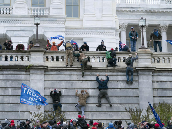Supporters of then-President Donald Trump climb the west wall of the U.S. Capitol on Jan. 6.