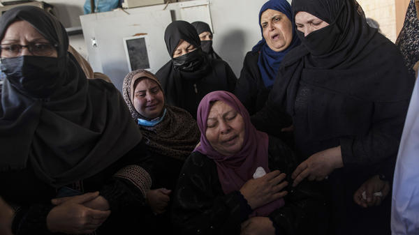 Relatives mourn over the bodies of four brothers who were found under the rubble of a destroyed house following Israeli airstrikes in Beit Lahiya in the northern Gaza Strip on Friday.