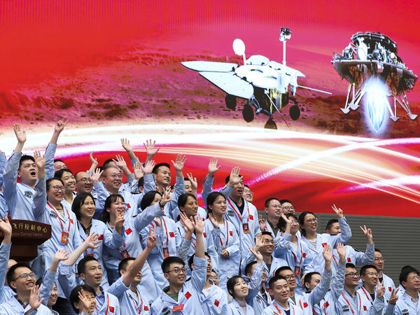 In this photo released by Xinhua News Agency, members at the Beijing Aerospace Control Center celebrate after China's Tianwen-1 probe successfully landed on Mars, at the center in Beijing on  Saturday.
