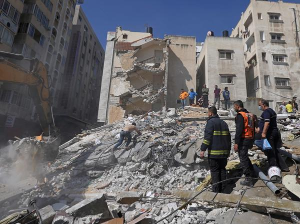People search for victims under the rubble of a destroyed building in Gaza City's Rimal residential district on Sunday, following Israeli airstrikes.