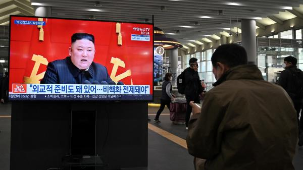 People watch a TV at Suseo train station in Seoul on March 26 as it shows file footage of North Korea's leader Kim Jong Un as a news program reports about the north's latest tactical guided projectile test.