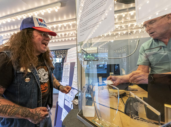 Darren Ford (left) reacts to the new mask guideline while presenting his vaccine card at Liberty Theatre on May 14 in Camas, Wash. Gov. Jay Inslee announced last Thursday that the statewide mask mandate would no longer apply to fully vaccinated adults.