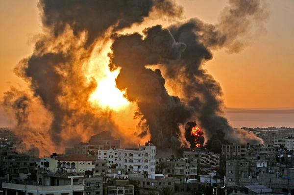 A fire rages at sunrise in the city of Khan Yunis following an Israeli airstrike in the southern Gaza Strip early on May 12.