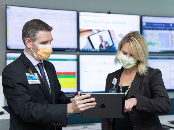 Dr. Michael Maniaci and Dr. Margaret Paulson confer at the Mayo Clinic's hospital-at-home command center in Jacksonville, Florida.