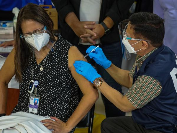 Philippines Health Secretary Francisco Duque III administers the China-made Sinovac COVID-19 vaccine to Eileen Aniceto, a doctor at the Lung Center of the Philippines.