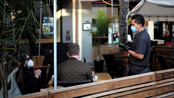 A staff member wearing a mask serves customers at a restaurant in San Mateo, Calif., on May 17.