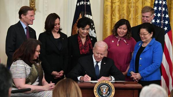 President Biden signs into law the COVID-19 Hate Crimes Act on Thursday in the East Room of the White House.