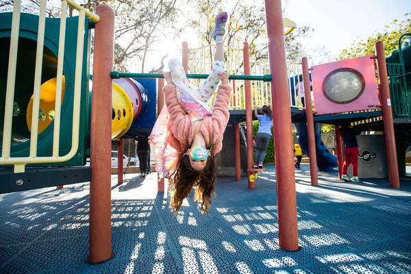 A student wears a mask while swinging around with her kindergarten class this month at Kenter Canyon School in Los Angeles.