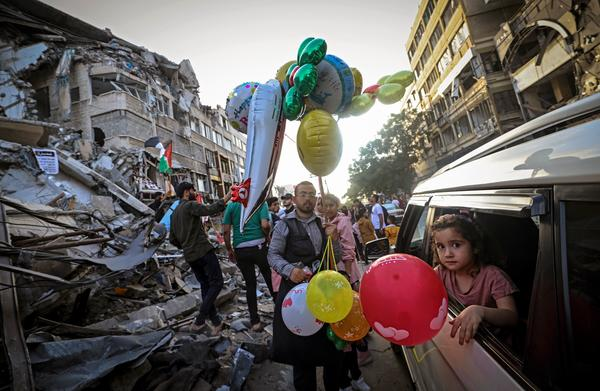 A Palestinian man sells balloons on Friday in Gaza City in front of the Al-Shuruq building, which was destroyed by an Israeli air strike.