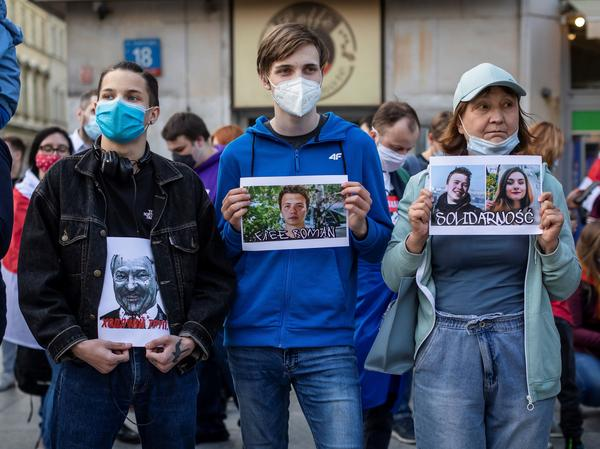 Protesters hold images of Belarus strongman Alexander Lukashenko, Belarus opposition activist Roman Protasevich and Protasevich's partner Sofia Sapega during a demonstration of Belarusians living in Poland and Poles supporting them in front of European Commission office in Warsaw on Monday.