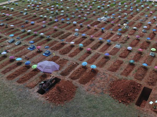A worker digs a grave in the San Juan Bautista cemetery in Iquitos, Peru, amid the coronavirus pandemic. On May 31, 2021, Peru announced a sharp increase in its COVID-19 death toll, saying there have been more than 180,000 fatalities since the pandemic hit the country early last year.