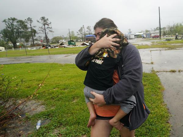 Danielle Fontenot runs to a relative's home in the rain with her son, Hunter, ahead of Hurricane Delta in Lake Charles, La., last October. The 2021 Atlantic hurricane season began June 1.