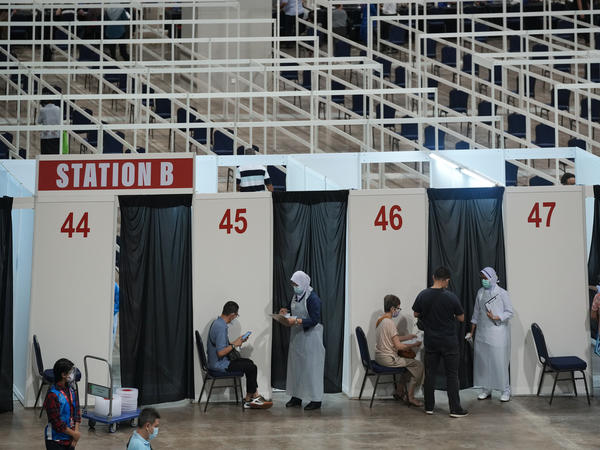 Health staff and patients at an exhibition center in Kuala Lumpur that's been turned into Malaysia's first mega-vaccination center. The government aims to speed up inoculations amid a sharp spike in infections.